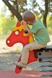Menino em um cavalo em um campo de jogos Imagens de Stock Royalty Free