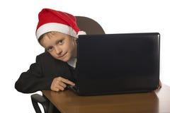 Menino em um chapéu de Santa Claus no computador Foto de Stock Royalty Free