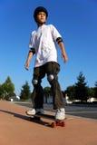 Menino em um skate Foto de Stock Royalty Free