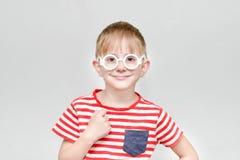 Menino em um t-shirt listrado e em vidros em um fundo branco Imagens de Stock Royalty Free