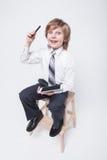 Menino em um terno e em um laço de negócio que guardam uma tabuleta foto de stock
