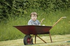 Menino em um wheelbarrow fotografia de stock royalty free