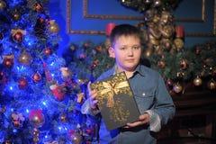 Menino em uma camisa da sarja de Nimes com um presente nas mãos Fotografia de Stock