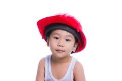 Menino em uma camiseta interioa branca que veste o capacete vermelho Foto de Stock