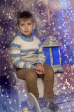 Menino em uma camiseta morna que senta-se em um trenó Foto de Stock