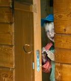Menino em uma casa de madeira. Fotografia de Stock Royalty Free