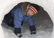 Menino em uma caverna da neve. Imagens de Stock Royalty Free