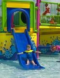 Menino em uma corrediça de água. Foto de Stock