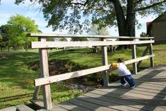 Menino em uma ponte de madeira pequena imagens de stock royalty free
