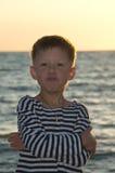 Menino em uma veste listrada em um fundo do mar Fotografia de Stock