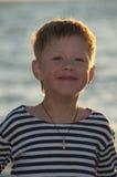 Menino em uma veste listrada em um fundo do mar Imagens de Stock