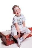 Menino encantador com a mala de viagem do marrom do vintage Imagens de Stock