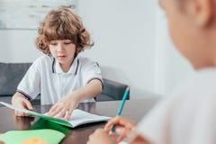 menino encaracolado adorável que faz trabalhos de casa com a irmã borrada imagens de stock royalty free