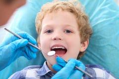 Menino encaracolado de Liittle que abre o seu boca largamente durante a inspeção da cavidade oral pelo dentista foto de stock