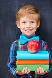 Menino encoureged de sorriso do gengibre que guarda uma pilha de Fotografia de Stock