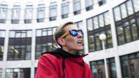 Menino energético em danças vermelhas da roupa e dos óculos de sol do esporte ao lado das colunas do granito vídeos de arquivo