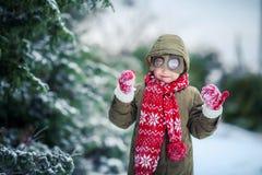 Menino engraçado da criança na roupa colorida que joga fora durante a queda de neve Lazer ativo com as crianças no inverno sobre foto de stock