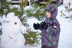 Menino engraçado da criança que faz um boneco de neve e que come a cenoura, jogando tendo o divertimento com neve, fora no dia fr Imagens de Stock