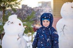 Menino engraçado da criança que faz um boneco de neve e que come a cenoura, jogando tendo o divertimento com neve, fora no dia fr Foto de Stock Royalty Free