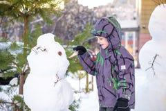 Menino engraçado da criança que faz um boneco de neve e que come a cenoura, jogando tendo o divertimento com neve, fora no dia fr Foto de Stock