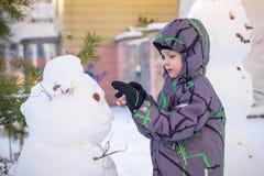 Menino engraçado da criança que faz um boneco de neve e que come a cenoura, jogando tendo o divertimento com neve, fora no dia fr Imagem de Stock Royalty Free