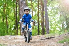 Menino engraçado feliz da criança na capa de chuva colorida que monta sua primeira bicicleta no dia frio na floresta Fotografia de Stock Royalty Free