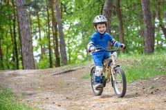 Menino engraçado feliz da criança na capa de chuva colorida que monta sua primeira bicicleta no dia frio no lazer ativo da flores Imagem de Stock Royalty Free