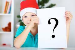 Menino engraçado no chapéu vermelho de Santa que guarda uma folha de papel com um marksign da pergunta Fotos de Stock