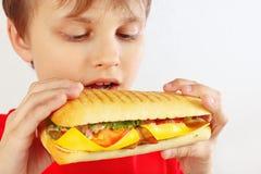 Menino engraçado no vermelho com um cheeseburger saboroso no fim branco do fundo acima foto de stock
