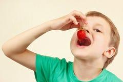 Menino engraçado novo que come a morango madura fresca Fotografia de Stock Royalty Free