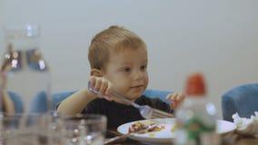 Menino engraçado pequeno com olhos grandes que come o prato disparatado 4K video estoque