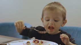 Menino engraçado pequeno com olhos grandes que come o prato disparatado 4K vídeos de arquivo