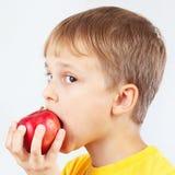Menino engraçado pequeno em uma camisa amarela que come a maçã vermelha foto de stock royalty free
