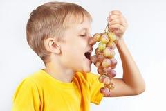 Menino engraçado pequeno em uma camisa amarela que come a uva fotografia de stock royalty free
