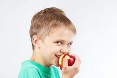 Menino engraçado pequeno em uma camisa verde que come a maçã vermelha Fotos de Stock Royalty Free