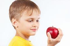Menino engraçado pequeno na camisa amarela com maçã vermelha fotografia de stock royalty free