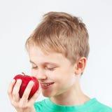 Menino engraçado pequeno na camisa verde com maçã vermelha Fotos de Stock Royalty Free