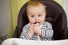 Menino engraçado pequeno que senta-se em uma cadeira para alimentar com bocal criançola sob a forma de um bigode Imagens de Stock