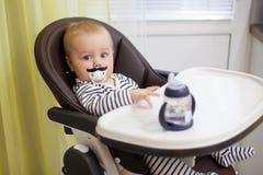 Menino engraçado pequeno que senta-se em uma cadeira para alimentar com bocal criançola sob a forma de um bigode Fotos de Stock Royalty Free