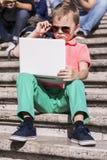 Menino engraçado que joga um portátil no verão foto de stock royalty free