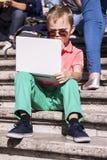 Menino engraçado que joga um portátil no verão foto de stock