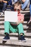 Menino engraçado que joga um portátil no verão imagem de stock royalty free
