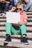 Menino engraçado que joga um portátil no verão imagens de stock