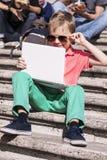 Menino engraçado que joga um portátil no verão fotos de stock
