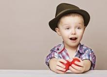 Menino entusiasmado da criança de 4 anos em um chapéu e em uma camisa que mantêm o vermelho das mãos do leste Fotografia de Stock