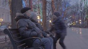 Menino entusiasmado feliz do neto que corre sobre às avós que sentam-se no banco no parque festivo da noite da atmosfera do Natal vídeos de arquivo