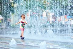 Menino entusiasmado que corre entre o volume de água no parque da cidade Fotografia de Stock Royalty Free