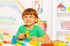 Menino esperto com o martelo do brinquedo na sala de aula imagens de stock royalty free