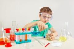 Menino esperto novo nos vidros de segurança que fazem experiências químicas no laboratório Foto de Stock