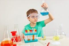 Menino esperto pequeno nos óculos de proteção de segurança que fazem experiências químicas no laboratório Foto de Stock Royalty Free